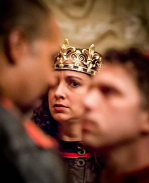 Henry in gold crown and brown leather tunic buttoned at the collar looks on worried at Gloucester and Winchester, nose-to-nose and out of focus in the foreground