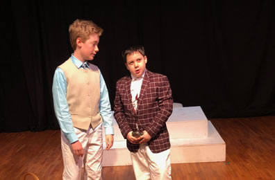 Bassanio in tan vest, light blue shirt, white slacks and a tie listens to Gratiano in a burgundy with checked jacket and white slacks, a flask in his hand.